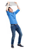 Man holding laptop above his head Stock Photo