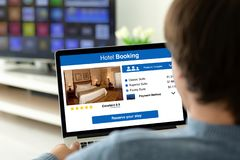 Man holding laptop with app hotel booking on the screen royalty free stock images