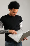 Man holding laptop computer. Portrait of young trendy latino man holding modern laptop computer Stock Photos