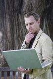 Man holding laptop computer. Young man studying a laptop computer in a park Royalty Free Stock Photos
