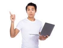 Man holding laptop computer and finger point up Royalty Free Stock Photo