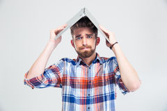Man holding laptop on his head like roof of house Royalty Free Stock Photo