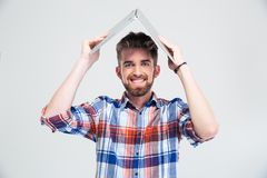 Man holding laptop on his head like roof of house Royalty Free Stock Photography