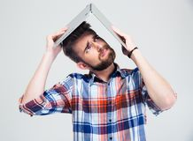 Man holding laptop on his head like roof of house Stock Images