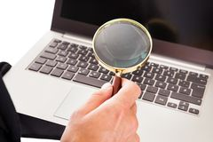 Man holding laptop and magnifying glass Stock Photography