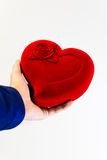 Man holding a large red symbol heart in hands. Man holding a big red heart symbol in a blue shirt Royalty Free Stock Photos
