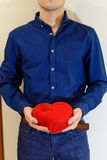 Man holding a large red symbol heart in hands. Man holding a big red heart symbol in a blue shirt Stock Image