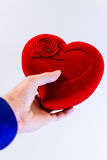 Man holding a large red symbol heart in hands. Man holding a big red heart symbol in a blue shirt Royalty Free Stock Photo