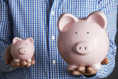 Man Holding Large And Small Piggy Bank Royalty Free Stock Photos