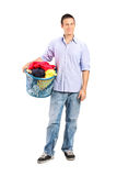 Man holding a laundry basket full of clothes Stock Photos