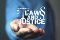 Man holding Law and Justice words with Scales and Paragraph symbol. stock images