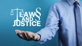 Man holding Law and Justice words with Scales and Paragraph symbol. royalty free stock image