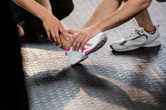 Man holding leg of an injured woman at the gym Royalty Free Stock Photos