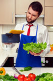 Man holding lettuce and pan with spaghetti Stock Image