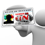 Man Holding License to Win as Identification Card. License to Win appears on this plastic laminated card as a person's access for opportunity in winning in life Royalty Free Stock Images
