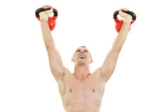 Man holding and lifting high up red kettlebells weights Royalty Free Stock Image