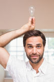 Man holding light bulb over his head Royalty Free Stock Image