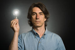 Man holding lighting bulb Stock Photos