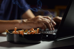Man holding lit and smoking cigarette. Between fingers and working on a laptop computer Stock Image