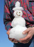 Man holding little snowman in his hands Stock Photo