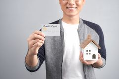 Man holding little wooden house in one hand and credit card in o. Ther. Looking at camera and smiling stock photo