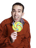 Man Holding Lollipop. A smiling man is holding a large lollipop, isolated against a white background Stock Photo