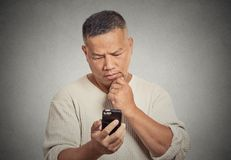 Man holding looking at his smart phone isolated gray wall background. Confused middle aged man holding using looking at his smart phone isolated on gray wall Stock Photo