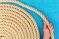 Man holding a loop of a coiled rope Stock Photo
