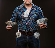 A man holding a lot of money. Banknotes of 100 dollars in different pockets, the concept of corruption. A man holding a lot of money. Banknotes of 100 dollars Stock Image