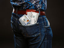 A man holding a lot of money. Banknotes of 100 dollars in different pockets, the concept of corruption. Royalty Free Stock Photos