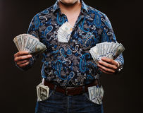A man holding a lot of money. Banknotes of 100 dollars in different pockets, the concept of corruption. Stock Photo