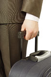 Man holding luggage. A suited man holding luggage waiting in a cue Stock Photo