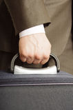 Man holding luggage. A suited man holding luggage waiting in a cue Royalty Free Stock Photo