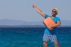 Man holding luggage and showing thumbs up against the blue ocean Stock Photography
