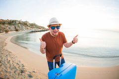 Man holding luggage and showing thumbs up against the blue ocean. Travel concept. Royalty Free Stock Image