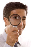 Man holding a magnifier. Over his eye stock image