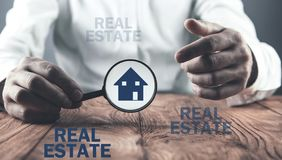 Man holding magnifier with house icon. Real estate stock photo
