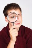 Man holding magnifier and looking through it Royalty Free Stock Images