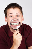 Man holding magnifier and showing teeth. Young man holding magnifier and showing teeth through it royalty free stock images
