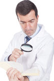Man holding a magnifying glass  and book Stock Photography