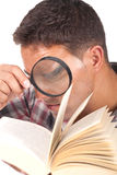 Man holding a magnifying glass and reading a book Stock Photo