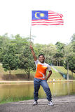 Man holding malaysia flag. A man  holding a nation flag for a Malaysia independence day with happy face reaction Royalty Free Stock Image