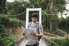 Man holding a map in middle of the forest stock photos
