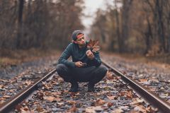 Man Holding Maple Leaf In The Middle Of Train Tracks During Day royalty free stock images
