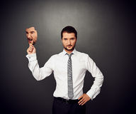 Man holding mask with bad mood. Serious businessman holding mask with bad mood Royalty Free Stock Photos