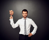 Man holding mask with crying face. Serious businessman holding mask with crying face Stock Images