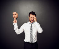 Man holding mask with serious face. Depressed man holding mask with serious face Stock Photography