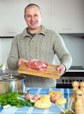 Man holding meat on cutting desk Royalty Free Stock Images