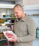 Man holding meat near fridge Stock Images