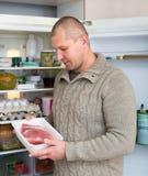 Man holding meat near fridge Stock Images